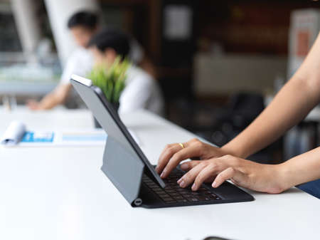 Close-up view of female typing on tablet keyboard while working on her project with her coworker in the background 版權商用圖片