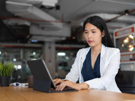 Cropped shot of young beautiful businesswoman typing on tablet keyboard while working in office room 版權商用圖片