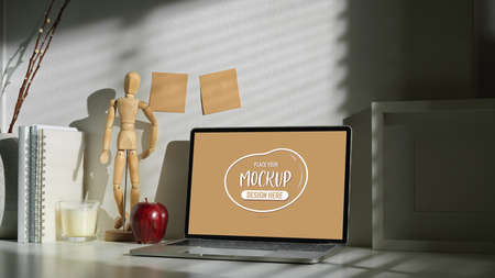 Cropped shot of artist workspace with mock up laptop computer with wooden figure and office accessories
