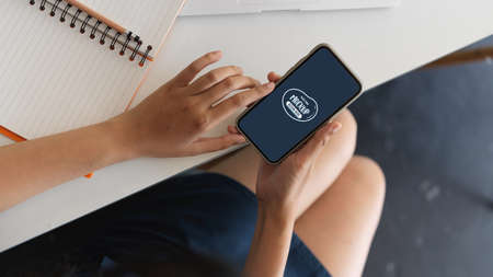 Close-up view of woman hand holding mock up smartphone in workspace 版權商用圖片