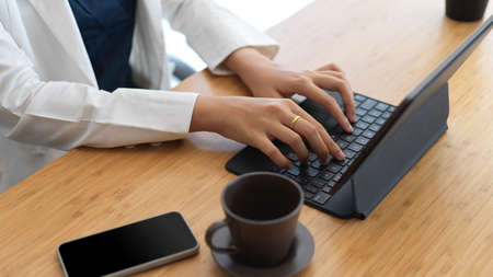 Close-up view of professional businesswoman typing on tablet keyboard while working her project 版權商用圖片