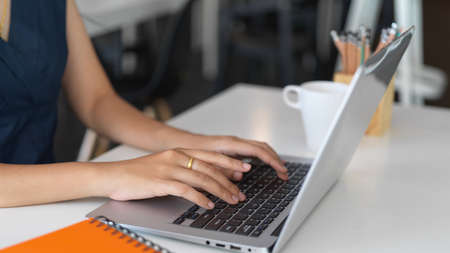 Cropped shot of young female typing on laptop computer while working on her project in office room