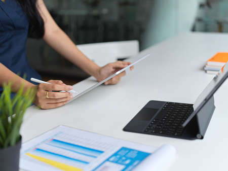 Cropped shot of businesswoman working on her project while using tablet in working space