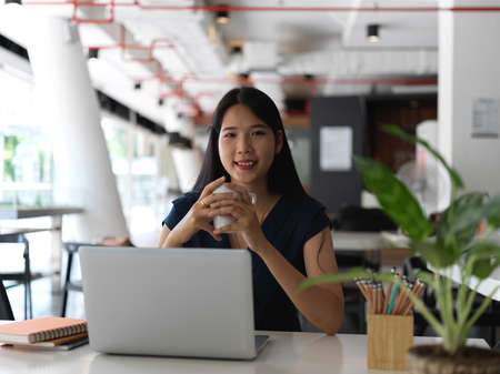 Portrait of young pretty asian businesswoman looking at the camera while holding coffee cup in workspace