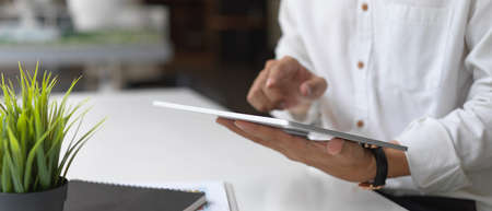 Cropped shot of businessman working on his project with tablet in office room