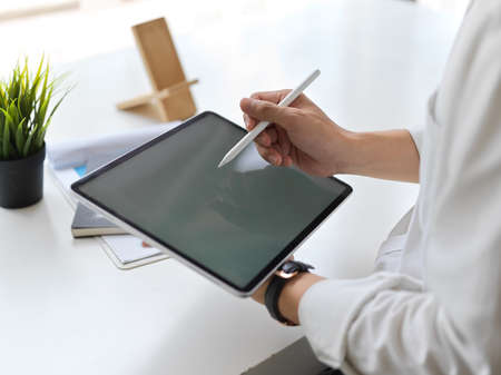 Cropped shot of young businessman writing on mock up tablet in modern office room