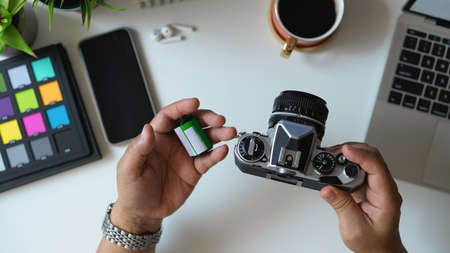 Top view of male photographer holding camera and camera film on his hand in workspace 版權商用圖片