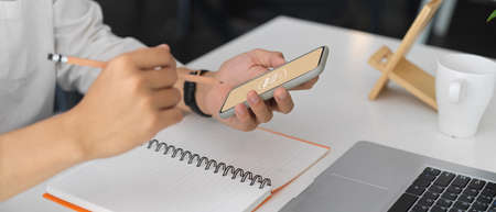 Cropped shot of businessman working on his idea with mock up smartphone while holding pencil to write down