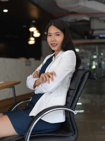 Portrait of young pretty businesswoman smiling to the camera while sitting in office room 版權商用圖片