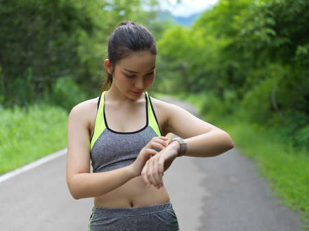 Young fit athlete watching the smartwatch to rate her training 版權商用圖片