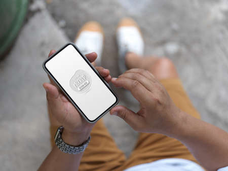 Top view of man holding mock up smartphone while standing outdoor