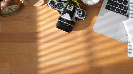 Overhead shot of comfortable workspace with camera, laptop computer and office supplies on wooden table 版權商用圖片