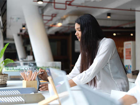 Close-up view of young businesswoman focusing on her project while using tablet