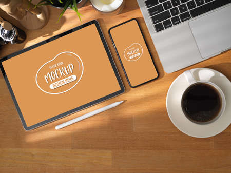 Top view of comfortable working table with mock up tablet and smartphone on wooden table with coffee cup