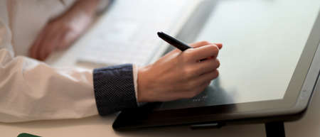 Close-up view of young woman drawing on Digital tablet in her workspace