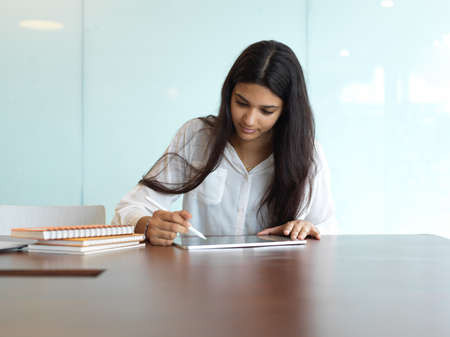 Young attractive businesswoman working on her project while using tablet in modern office room
