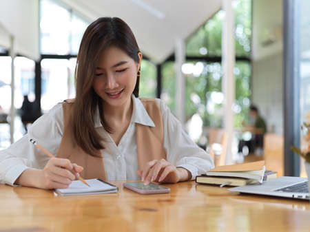 Portrait of female college student searching information on smartphone and write it down in notebook
