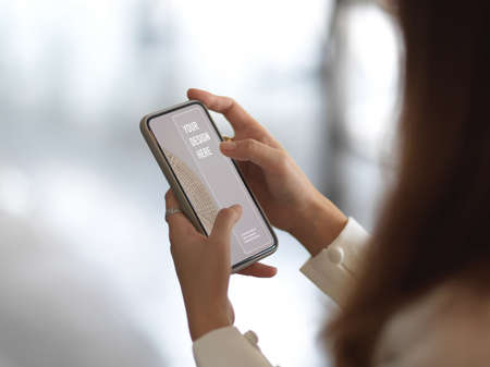 Side view of female hands using mock up smartphone in blurred background