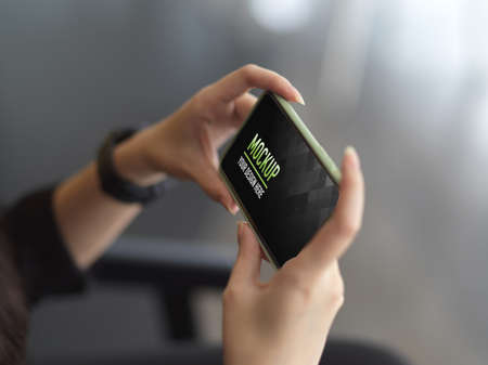 Side view of female hands holding horizontal smartphone in blurred background Stockfoto