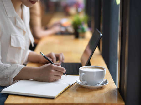 Side view of female hand writing on blank notebook while working with tablet on wooden bar