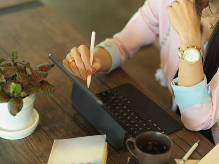 Cropped shot of female freelancer working with digital tablet on wooden table in cafe