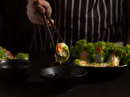 Close up view of female cook gripping  Vietnamese spring rolls with chopstick in dark background