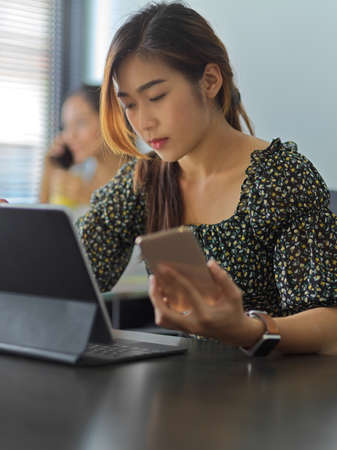 Portrait of female office worker working with smartphone and digital tablet in office room