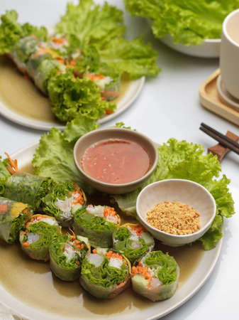 Cropped shot of Vietnamese spring rolls with dipping sauce and vegetable on dinning table 免版税图像