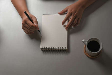 Top view of male hand writing on blank notebook on white table with coffee cup