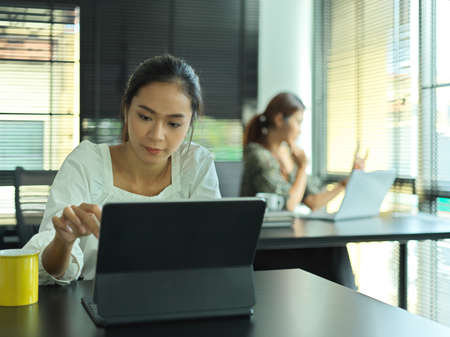 Portrait of female office worker working with digital tablet on worktable in office room