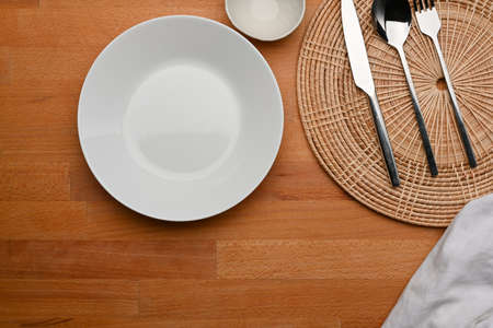 Top view of dinning table with mock up ceramic plate, cutlery, place mat and copy space