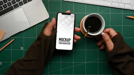 Overhead shot of male hand holding smartphone and coffee cup on cutting board