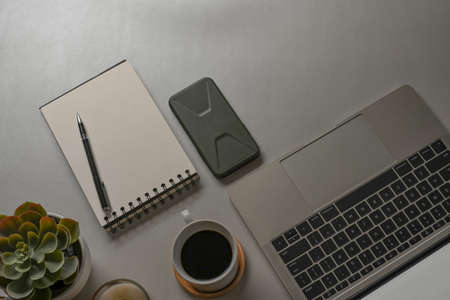 Top view of workspace with laptop, stationery, coffee cup and copy space on white desk 免版税图像