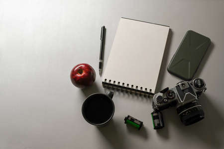 Top view of workspace with blank notebook, camera, supplies and copy space on white desk