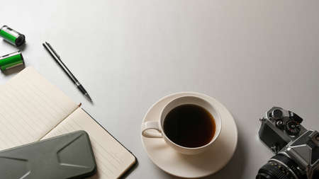 Top view of workspace with coffee cup, camera, stationery and copy space on white desk