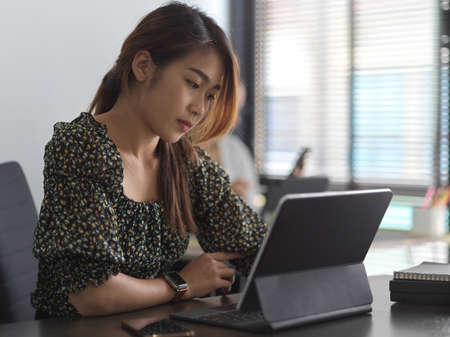 Side view of businesswoman working with digital tablet in meeting room