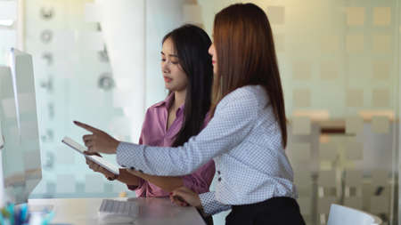 Side view of two businesswomen working together with computer device in office room 免版税图像