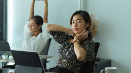Portrait of two businesswoman lying relaxed on back chair in modern office room