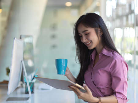Side view of businesswoman drinking coffee while reading information on digital tablet