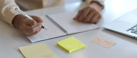 Close up view of male hand writing on blank notebook on white worktable with laptop and stationery