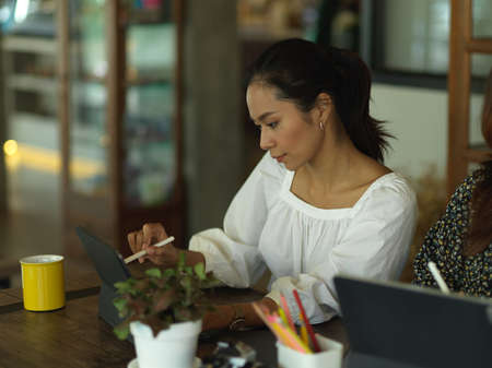 Portrait of businesswoman working with tablet while sitting next to coworker in office room 免版税图像