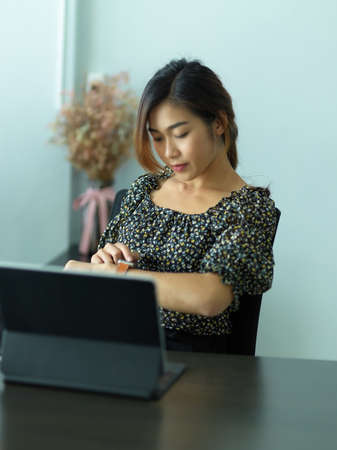 Portrait of female checking message on smartwatch while working in office room
