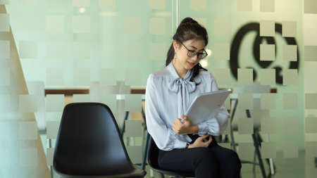 Portrait of businesswoman holding document file while waiting for interview
