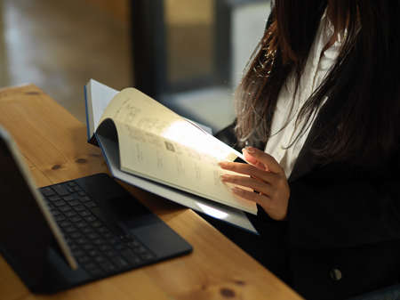 Side view of female student hand opening textbook while reading to prepare for her coming exam Stock Photo