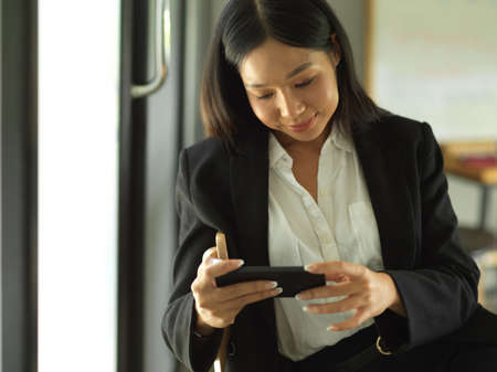 Portrait of businesswoman using horizontal smartphone while relaxing in cafeteria
