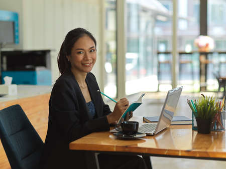 Portrait of businesswoman smiling to camera while working with schedule book and laptop in office room