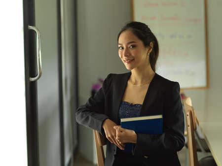Portrait of businesswoman smiling to camera and holding textbook while sitting in library