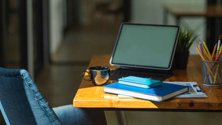 Cropped shot of home office desk with books, stationery, paperwork and digital tablet on wooden table