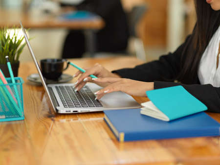 Side view of businesswoman hand typing on laptop keyboard on wooden table with stationery