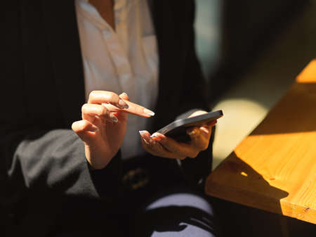 Close up view of female texting on smartphone in her hand while relaxed sitting in cafeteria